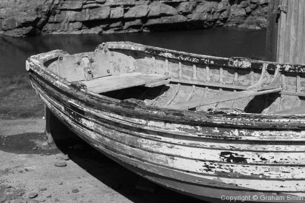 Black and white rowing boat next to a stone beach